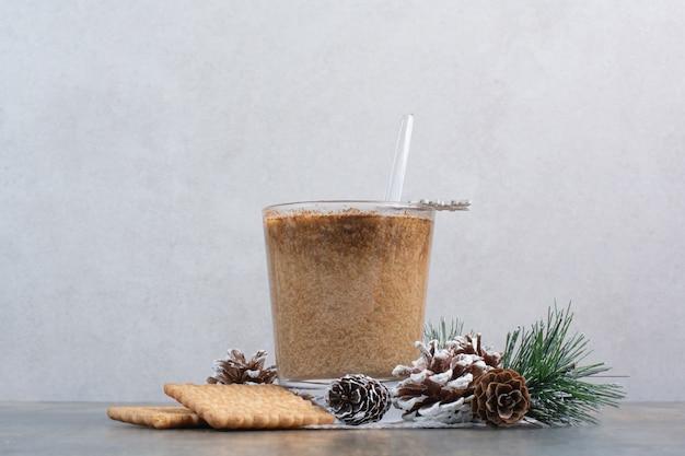 Xícara de café com saborosos biscoitos e pinhas em fundo de mármore. foto de alta qualidade