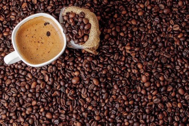 Xícara de café com saco de café na mesa de madeira. ver de cima