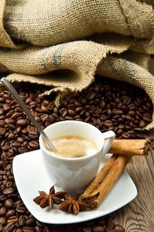 Xícara de café com saco de serapilheira de feijão assado na mesa rústica