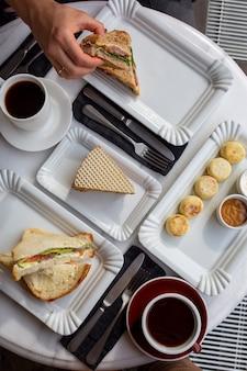 Xícara de café com sobremesa na mesa de mármore. dia do café. café da manhã em um fundo branco. bebida quente com bolo. vista superior do café aromático. café preto com comida. café da manhã em um café. dia da comida