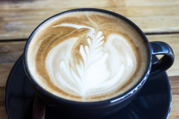 Xícara de café com sol da manhã na mesa de madeira