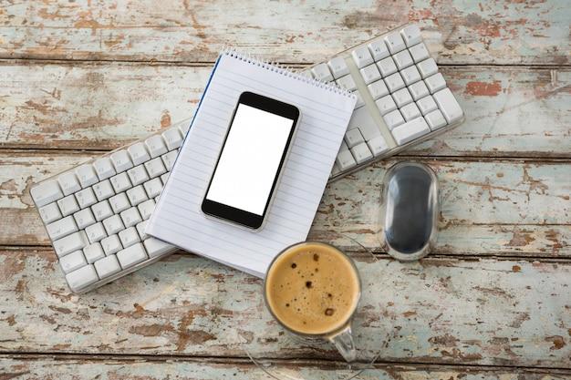 Xícara de café com teclado, celular e mouse