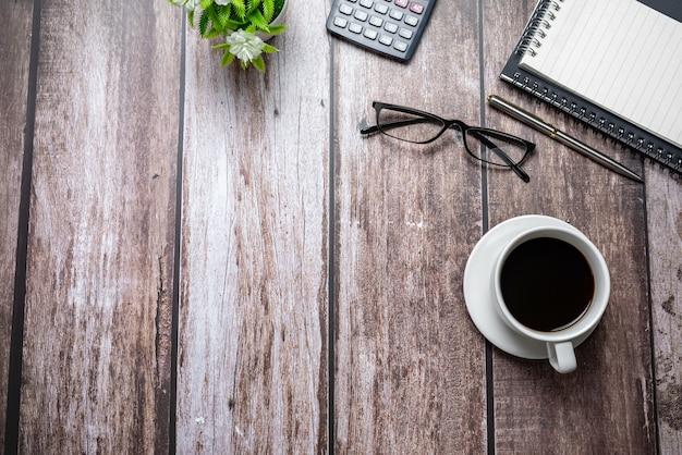 Xícara de café com todos os suprimentos em uma mesa de madeira. copie o espaço.