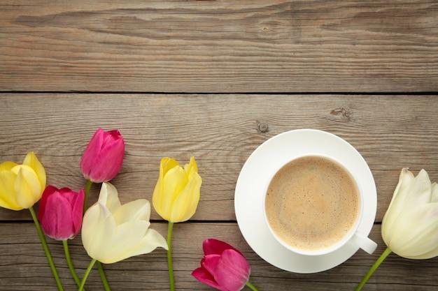 Xícara de café com tulipas na superfície cinza de madeira com espaço de cópia