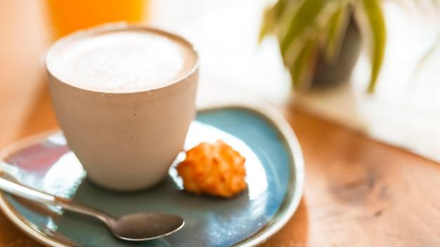 Xícara de café com um biscoito doce