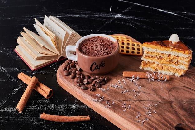 Xícara de café com uma fatia de bolo de caramelo.