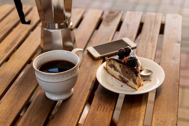Xícara de café com uma fatia de bolo na mesa