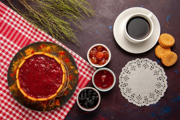 Xícara de café com vista de cima com deliciosos biscoitos de bolo de sobremesa e geleias de frutas na superfície escura.