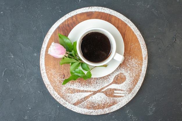 Xícara de café com vista de cima com flor na mesa escura