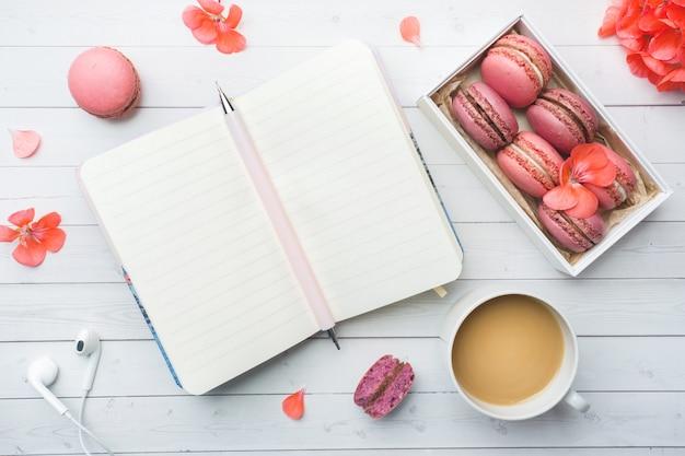 Xícara de café, cookies de biscoito em uma caixa, flores e um notebook com lay plana