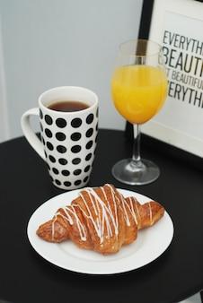 Xícara de café, croissant e suco de laranja na mesa preta