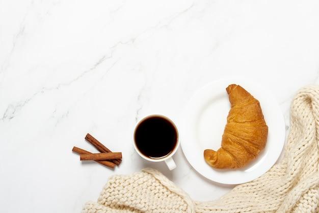 Xícara de café, croissant em um prato e um lenço de malha, canela em pau em uma mesa de mármore