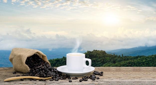 Xícara de café da manhã e vista para grãos de café torrados com sol da montanha