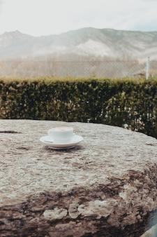 Xícara de café da manhã em uma velha mesa de pedra com fundo de montanha ao nascer do sol