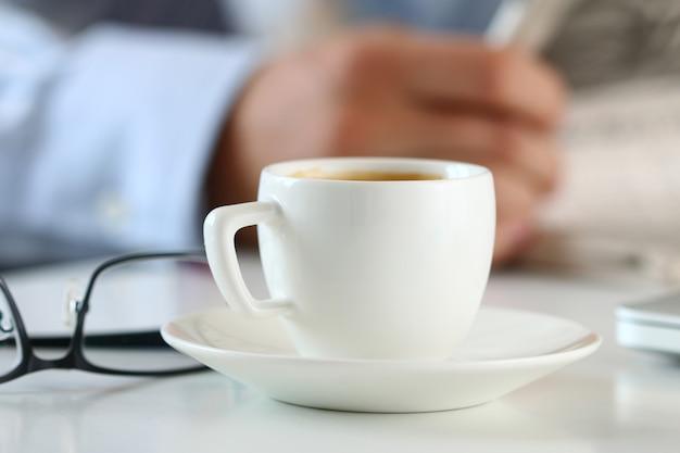 Xícara de café da manhã na mesa de trabalho com analista de negócios segurando nas mãos e lendo jornal