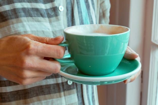 Xícara de café da manhã nas mãos de uma jovem