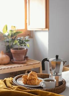 Xícara de café de ângulo alto e croissants