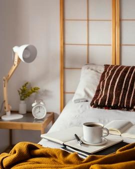 Xícara de café de ângulo alto na cama