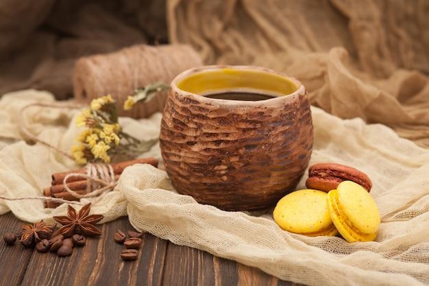 Xícara de café de barro, biscoitos, canela em um marrom de madeira