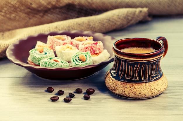 Xícara de café de barro com grãos de café e manjar turco deitado no prato de barro na placa de madeira