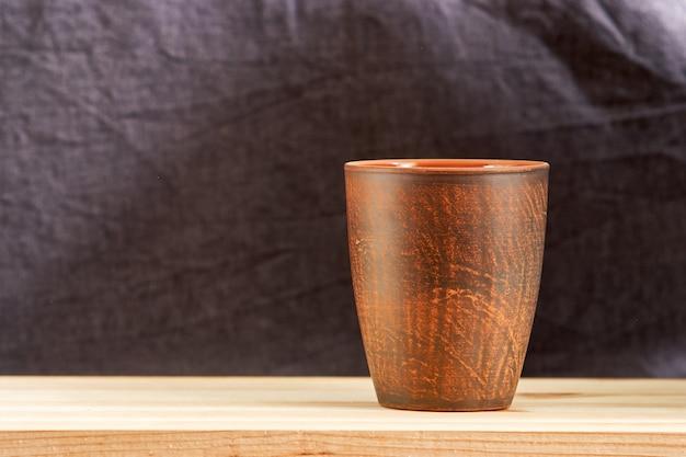 Xícara de café de barro no fundo da mesa de madeira