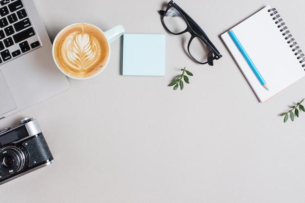 Xícara de café de cappuccino; computador portátil; câmera retro; bloco de notas adesivo; óculos e lápis no bloco de notas em espiral contra o pano de fundo branco