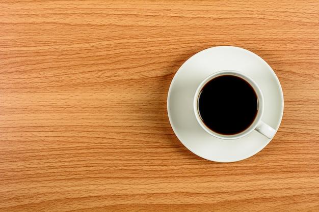 Xícara de café de cerâmica branca na mesa de madeira.