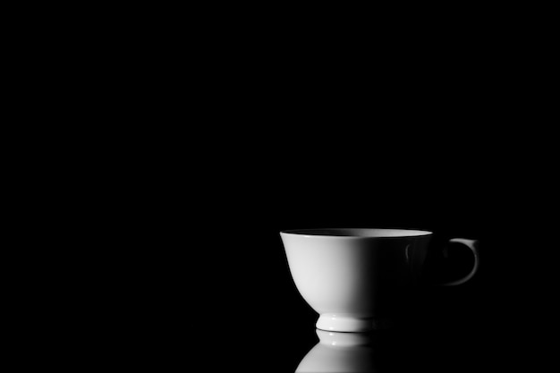 Xícara de café de cerâmica branca no escuro.