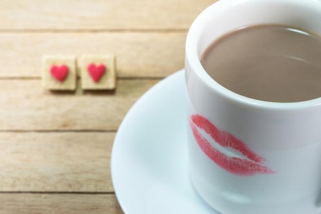 Xícara de café de cerâmica com marca de batom no fundo madeira