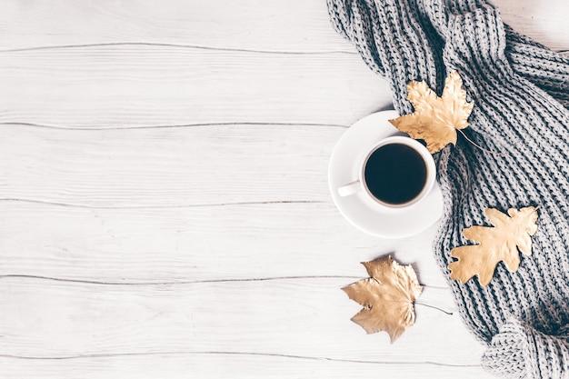Xícara de café de composição aconchegante de outono e folhas douradas na mesa de madeira branca. vista do topo. postura plana. copie o espaço.