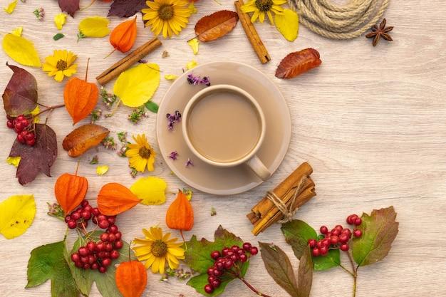 Xícara de café de composição de outono em uma mesa com flores e folhas imagem de plano de fundo vista superior