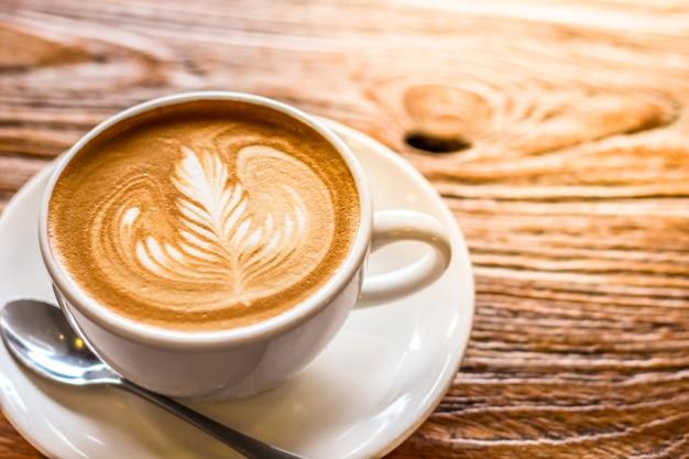 Xícara de café de latte art com colher e prato na mesa marrom com bela luz quente