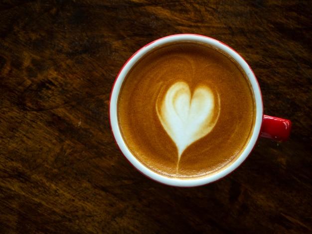 Xícara de café de latte art de coração de amor