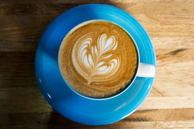 Xícara de café de latte art na mesa de madeira, vista superior