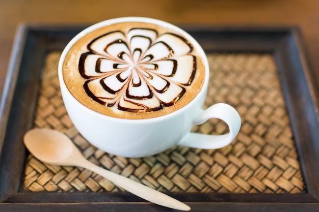 Xícara de café de latte art na placa de madeira