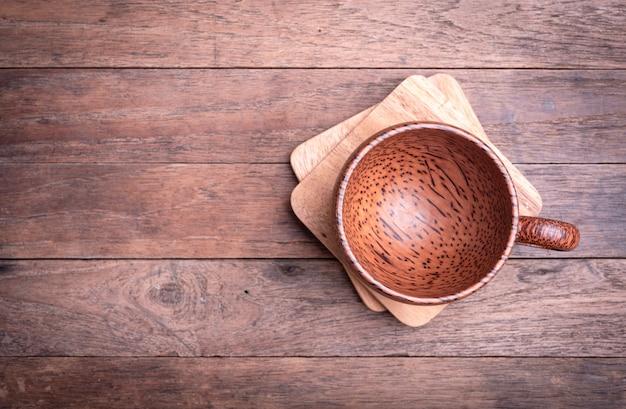 Xícara de café de madeira e placa de madeira em branco sobre fundo de mesa de madeira de grunge, vista superior com espaço de cópia