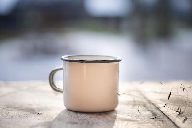 Xícara de café de metal branco, caneca na velha mesa de madeira