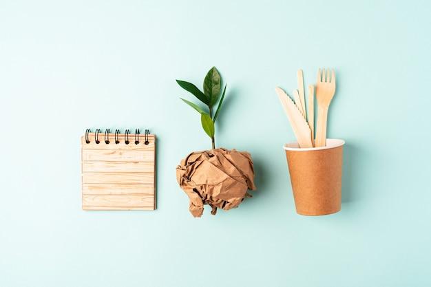 Xícara de café de papel artesanal, broto de folhas verdes e vista superior de talheres reciclados. flat lay zero desperdício, conceito livre de plástico orgânico natural, ecologicamente correto. talheres de terra, biodegradáveis com espaço de cópia.