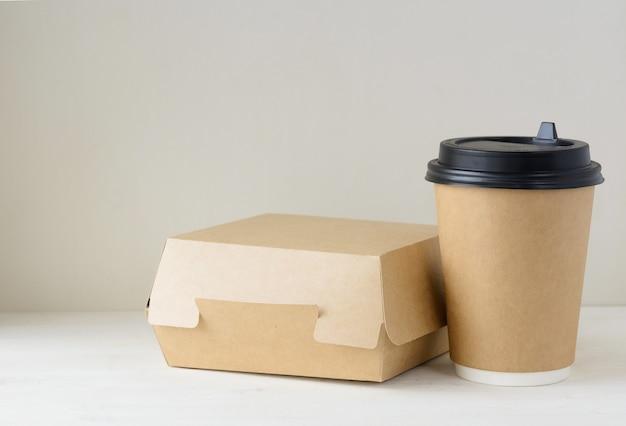 Xícara de café de papel artesanal e caixa de comida na mesa branca