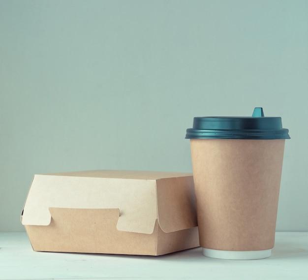 Xícara de café de papel artesanal e caixa de comida na mesa