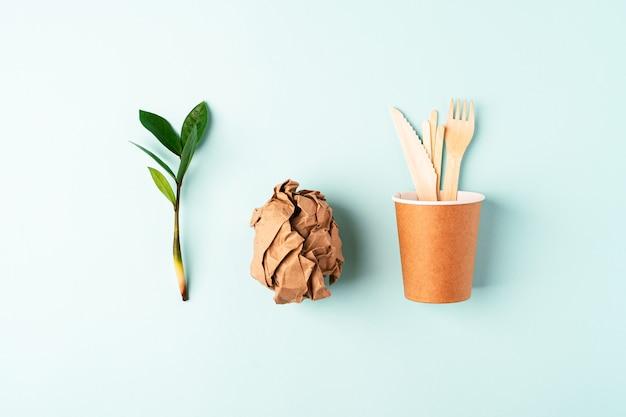 Xícara de café de papel artesanal, folhas verdes e vista superior de talheres reciclados. flat lay zero desperdício, conceito livre de plástico orgânico natural, ecologicamente correto. talheres de terra, biodegradáveis com espaço de cópia.