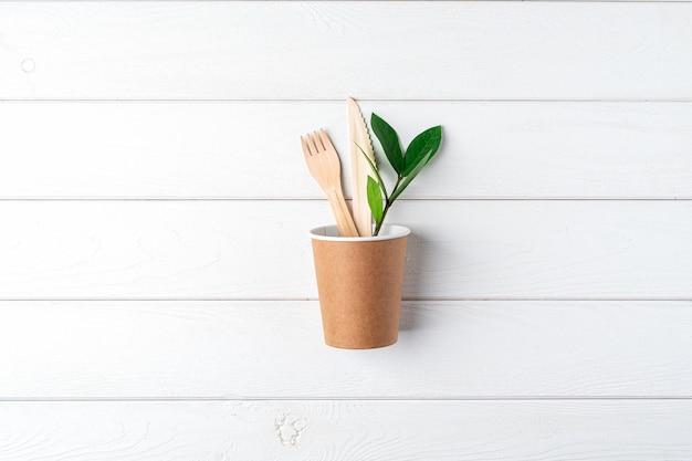 Xícara de café de papel artesanal, folhas verdes e vista superior de talheres reciclados. flat lay zero waste, eco