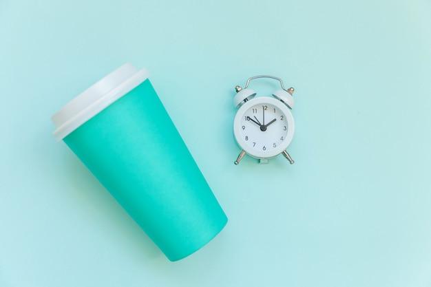 Xícara de café de papel azul de design simplesmente plana leigos e despertador isolado em azul pastel colorido