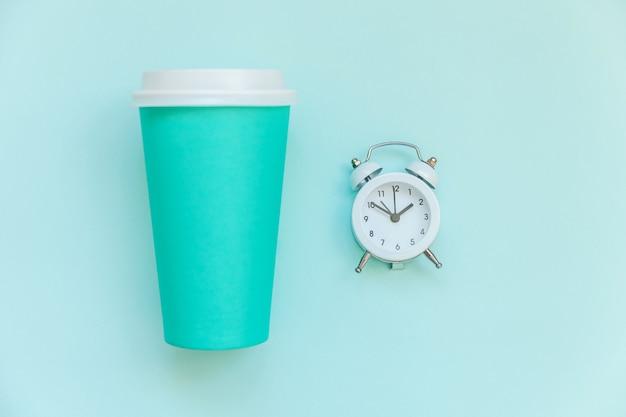 Xícara de café de papel azul de design simplesmente plana leigos e despertador isolado em fundo colorido pastel azul