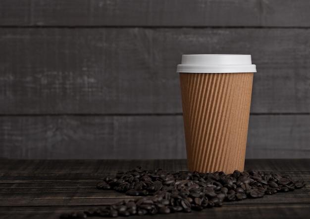 Xícara de café de papel com cappuccino e grãos de café sobre fundo de madeira