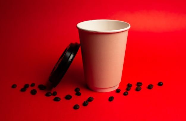 Xícara de café de papel com tampa aberta e grãos de café em um fundo vermelho