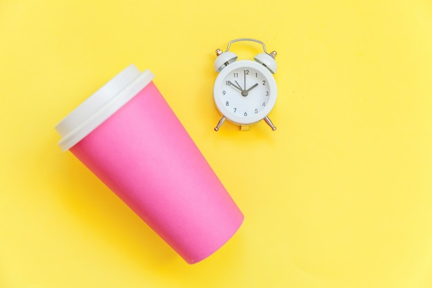 Xícara de café de papel-de-rosa de design simplesmente liso leigos e despertador isolado em fundo moderno colorido amarelo