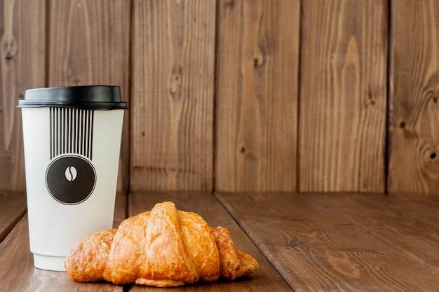 Xícara de café de papel e croissants em fundo de madeira