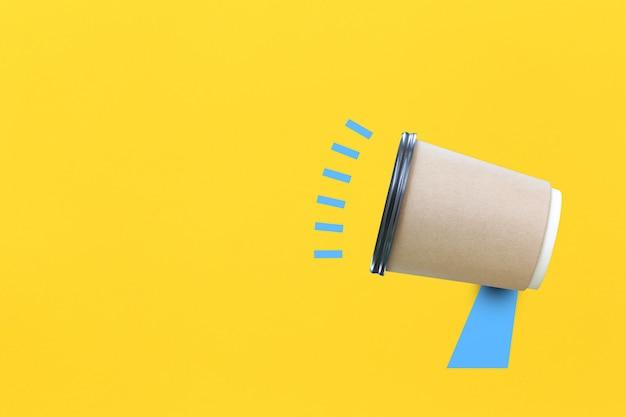 Xícara de café de papel inventada como um megafone em fundo de papel amarelo para design em seu conceito de trabalho.