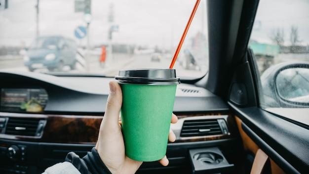 Xícara de café de papelão verde no carro nas mãos bebida na viagem